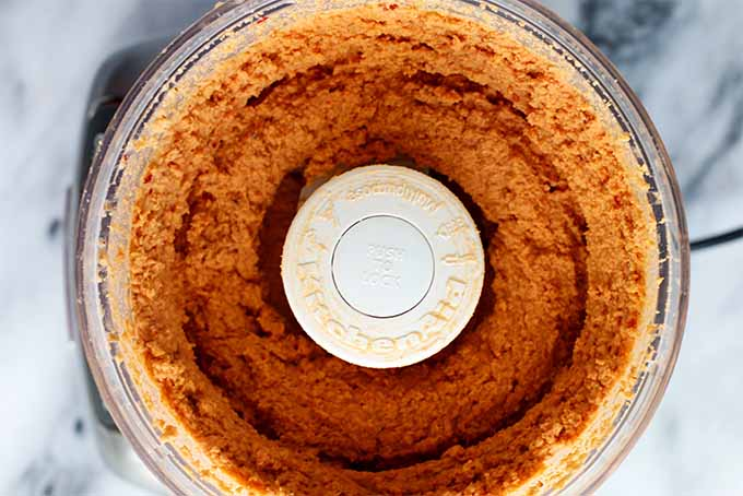 Top-down view of an open food processor filled with orange-colored homemade hummus, on a gray and white marble background.