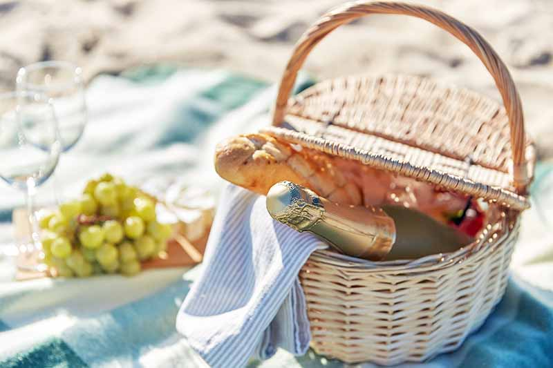 A light beige wicker basket containing a bottle of champagne, a baguette, and a cloth napkin is in the foreground, with a pale blue-green blanket spread on teh sand in the background, with a small wooden cutting board on it with a bunch of green grapes and a small wheel of cheese with a white rind on top of that, and two wine glasses.