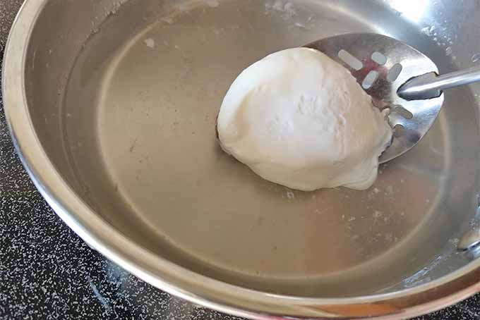 A metal slotted spoon scoops a poached egg out of a frying pan of water.