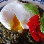 Closeup of a poached egg broken to expose the soft-cooked yolk, on a bed of steamed spinach with red pimiento peppers and a sprig of basil, on a white and blue willow patterned plate.