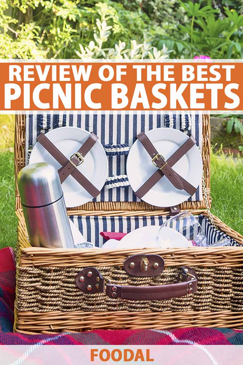 Vertical image of a wicker suitcase-style picnic basket with a handle on the front, fully stocked with dishes, flatware, a metal thermos, and other items, on a red blanket spread out on green grass, with a tree in the background, in bright sunshine, printed with orange and white text near the top and at the bottom of the frame.