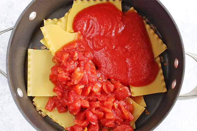Top-down view of a large nonstick frying pan filled with uncooked lasagna noodles, chopped tomatoes, and tomato sauce.