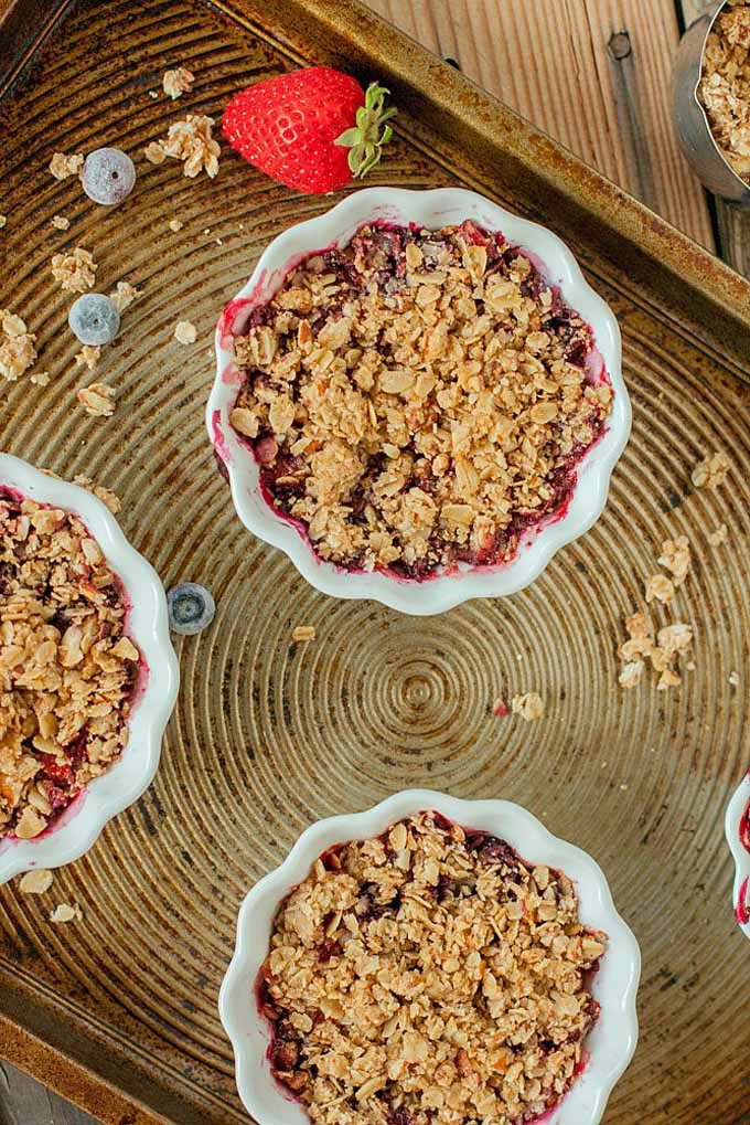 Top-down view of a fluted white ceramic custard cup of baked berry crumble with red berry juice and an oat crumble topping, on a brown baking sheet with scattered crumble topping and fresh blueberries and one whole strawberry, on a brown wood surface.