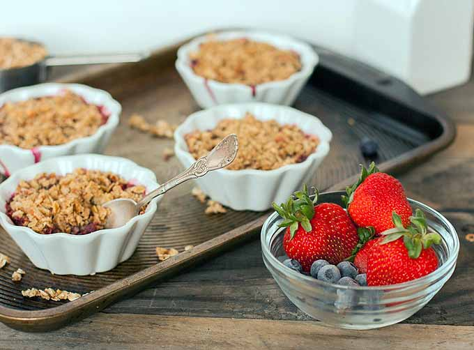 Four white ceramic custard cups baked with an almond oatmeal crumble topping on a baking sheet, next to a small glass bowl of fresh blueberries and strawberries on a brown wood table.