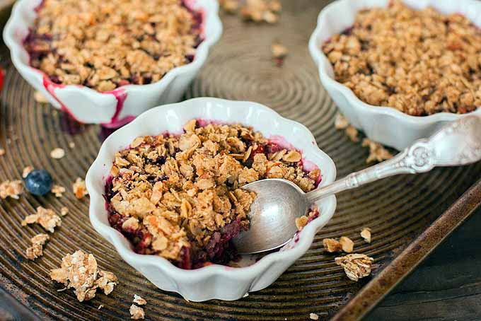 Top-down view of three white ceramic custard cups with ruffled edged filled with a baked berry crumble dessert, with scattered crumble topping and blueberries on a baking sheet, with a spoon stuck into one of the desserts.