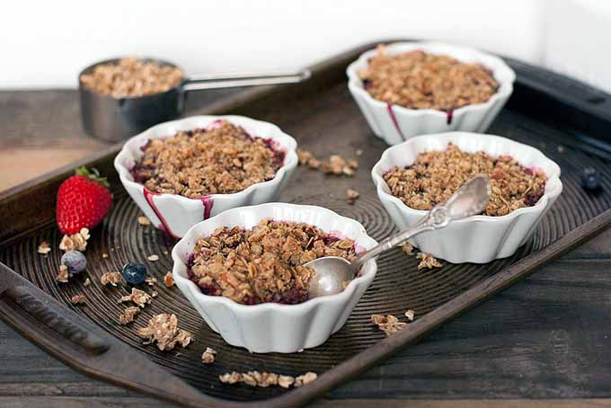 Four mini berry crumbles in white custard cups on a baking sheet, with scattered crumble topping, blueberries, and a whole strawberry, with a silver spoon stuck into the dessert in the foreground, on a brown wooden table in front of a white wall, with a silver measuring cup full of oats in the background.