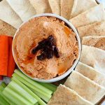 Top-down view of a dip bowl filled with light orange sun-dried tomato hummus, on a platter surrounded with fanned out pita bread sliced into triangles, orange carrot sticks, and pale green celery sticks, on a mottled pale blue background.