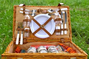 Horizontal closely cropped image of a fully stocked wicker picnic basked with glasses, silverware, dishes, and more, on a green lawn.