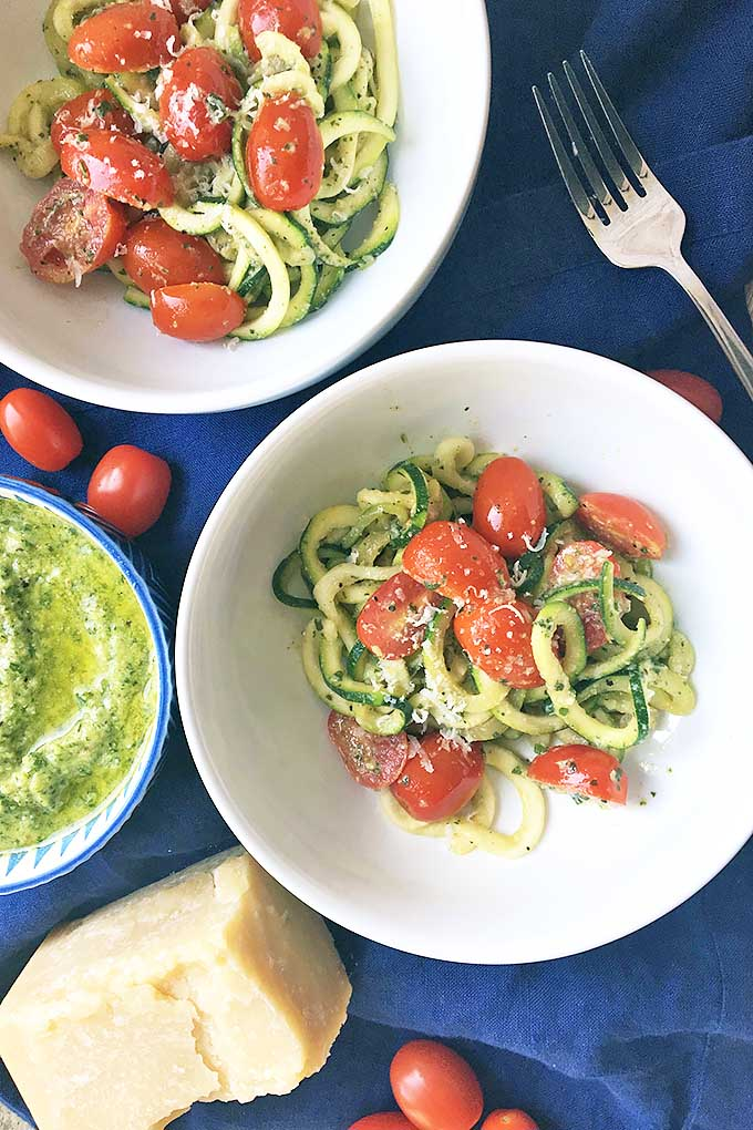 Vertical image of white bowls with zucchini, tomatoes, and pesto.