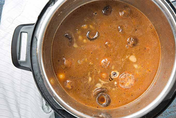 Top-down image of a beef stew cooking in a slow cooker.