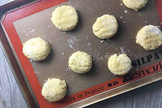 Horizontal image of a sheet pan lined with a silicone mat with cookie dough portions.