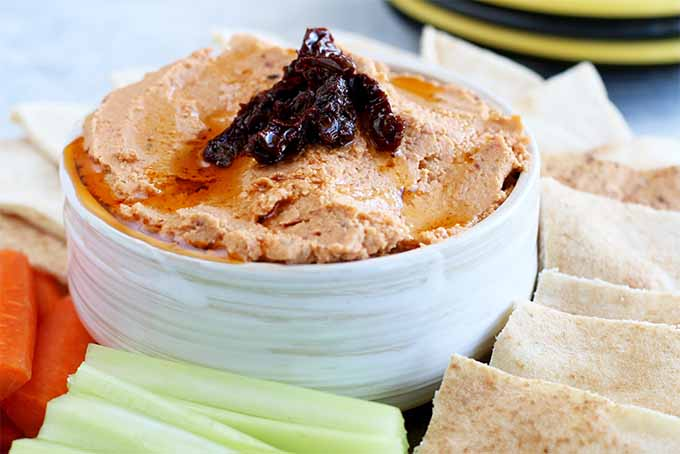 Closeup of a white ceramic dip bowl filled with sun-dried tomato hummus topped with more oil-packed sun-dried tomatoes for garnish, on a platter surrounded by sliced pita bread, carrot sticks, and celery sticks, on a gray surface with a navy blue and yellow striped plate at the top right corner of the frame.