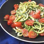 Horizontal image of a pan with a mixture of zoodles and tomatoes on a blue towel.