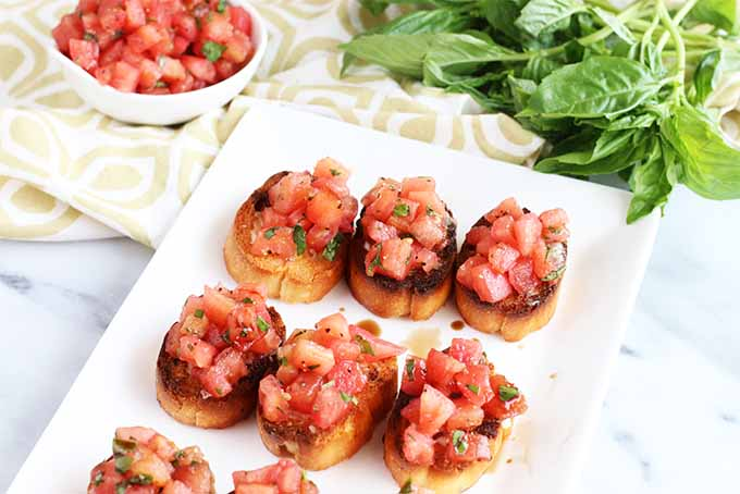 Homemade tomato basil bruschetta on a white rectangular serving dish, with a folded beige and white patterned cloth napkin topped with a small bowl of chopped tomatoes and sprigs of fresh basil in the background, on a white marble surface.