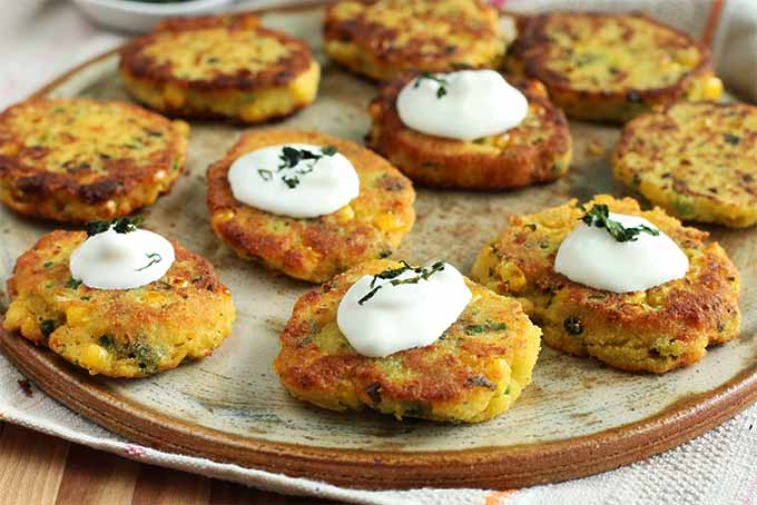 Ten corn and cheese arepas arranged on a brown and tan serving platter, half of which are topped with sour cream and cilantro.