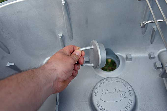 A human hand is removing the ash plug at the back of the PK360.