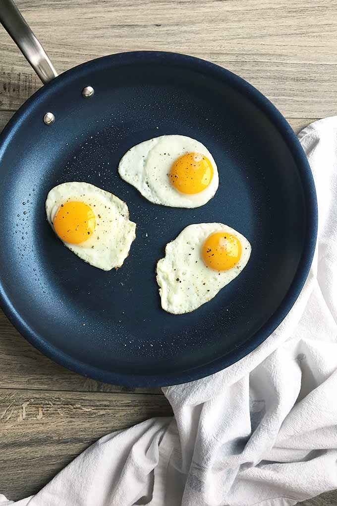 Vertical image of a nonstick skillet with fried eggs on a white towel.