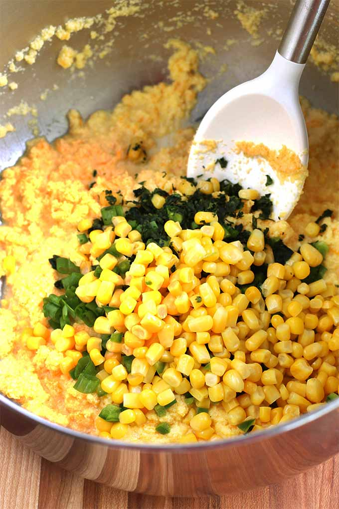 A stainless steel bowl of cornmeal, yellow corn kernels, and chopped jalapeño and cilantro, with a white rubber spatula.