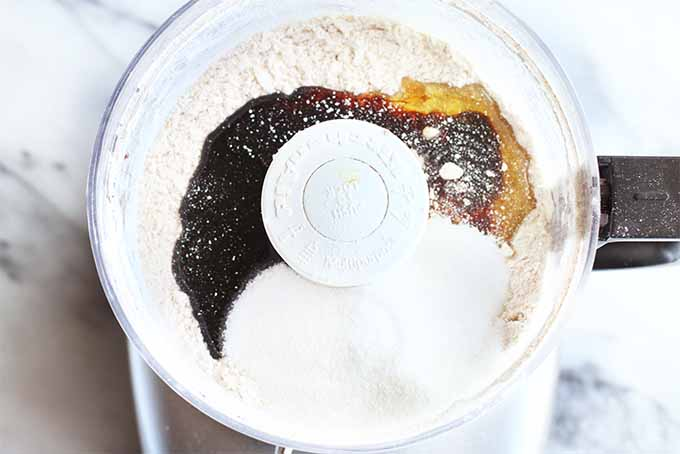 Top-down shot of a food processor canister filled with flour, molasses, honey, and other ingredients for making a graham cracker dough, on a white marble background with gray veins.