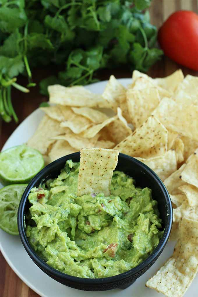 A black plastic bowl of green guacamole studded with diced tomato, with a chip stuck into the bowl, on a large white plate with more tortilla chips and juiced lime halves, with cilantro and whole tomatoes in the background, on a brown wooden table.