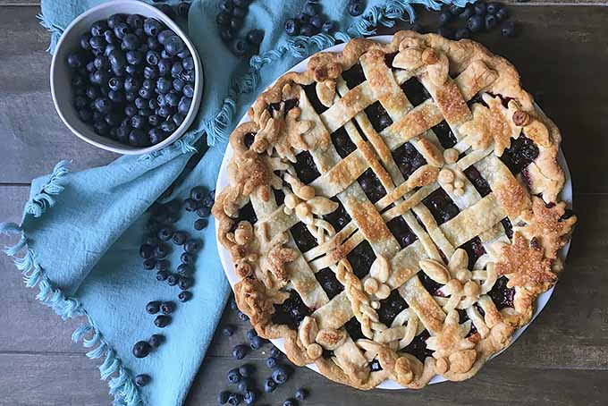 Horizontal image of a whole baked pie on a blue towel with blueberries.