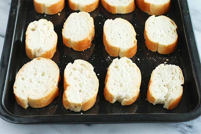 Half-inch baguette slices arranged in rows so they are not touching, on a small metal rimmed baking sheet.