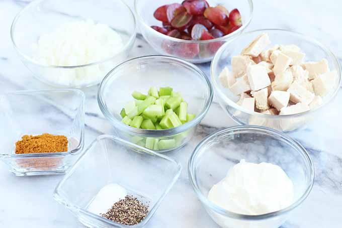 All of the ingredients required to make curry chicken salad, prepped and arranged on a marble surface in small glass dishes - red grapes, cooked chicken breast, yogurt, celery, onion, salt and pepper, and curry powder.
