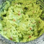 A gray stone molcajete full of homemade guacamole with bits of onion and tomato.