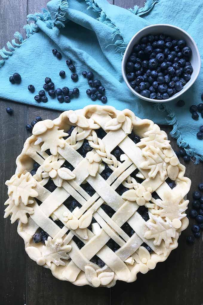 Vertical image of a whole unbaked pie on a blue towel with a bowl of blueberries.