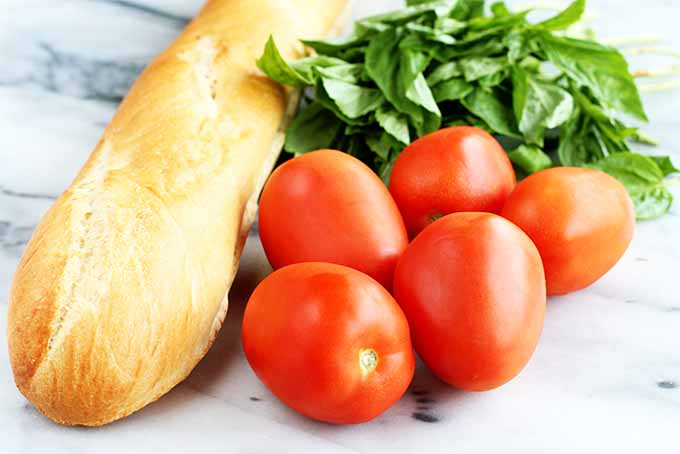 A baguette, a bunch of fresh green basil, and five red Roma tomatoes, on a marble surface.