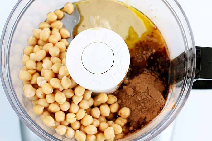 Top-down closely cropped shot of a food processor that contains chickpeas, oil, tahini, vanilla extract, maple syrup, and vanilla, on a white background.