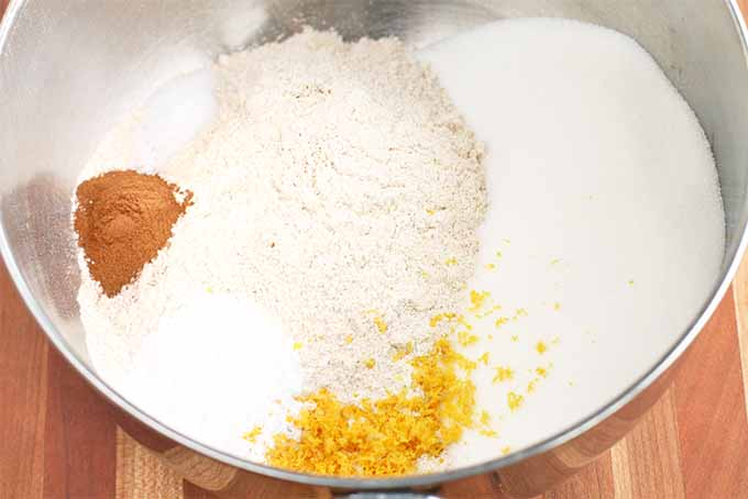 Closeup of a stainless steel mixing bowl that contains spelt flour, cinnamon, almond meal, sugar, salt, baking powder, and lemon zest, on a brown wood background.