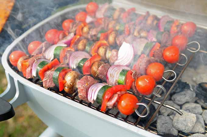 Lamb, mushroom, tomato, bell pepper, zucchini, and onion skewers being grilled on a Portable Kitchen PK360 grill.