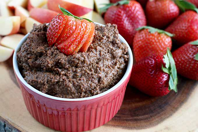 A red and white ramekin of brown dark chocolate hummus topped with a sliced strawberry, on a wooden display board with more strawberries and apple slices with red peels.