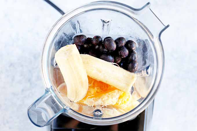 Top-down shot of a clear plastic blender pitcher filled with blueberries, bananas, and orange segments, on a black blender base with a black cord, on a white background.