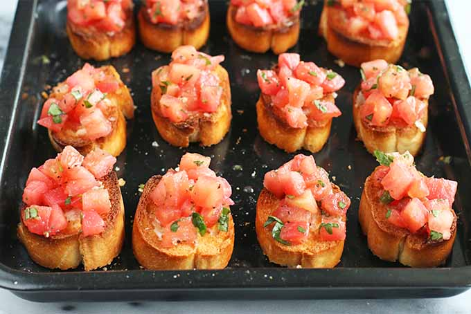 Three rows of four pieces of tomato and basil bruschetta on a small black rimmed baking sheet.