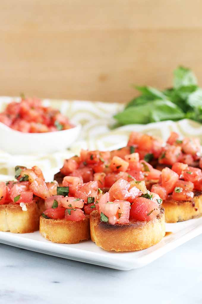 Oblique view of a square serving dish of bruschetta, on a marble surface with a beige background, beside a small white bowl of tomato topping and a sprig of fresh basil.