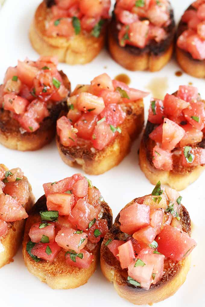 Closely cropped downward shot of nine pieces of bruschetta arranged in a grid on a white plate.