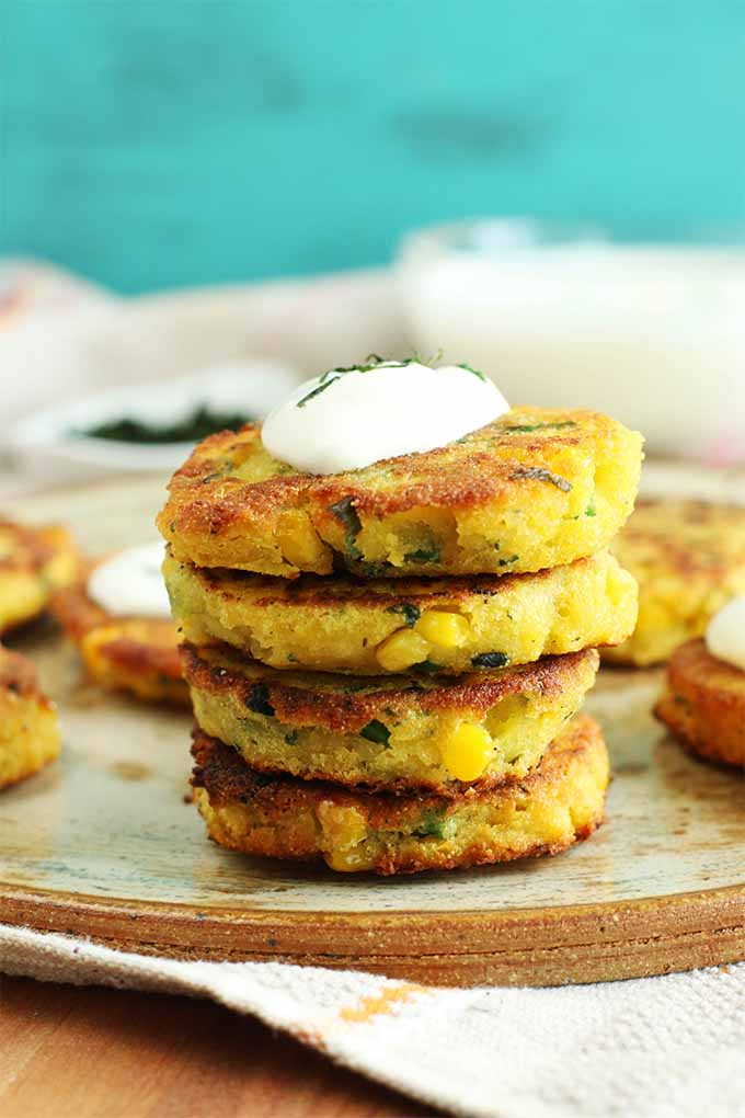 Four corn and cheese arepas are stacked and topped with a dollop of sour cream and some chipped cilantro, on a tan plate with a brown rim, with more corn cakes arranged behind them, with a small white dish of chopped cilantro and a bowl of sour cream on a beige cloth in soft focus against a robin's egg blue wall.