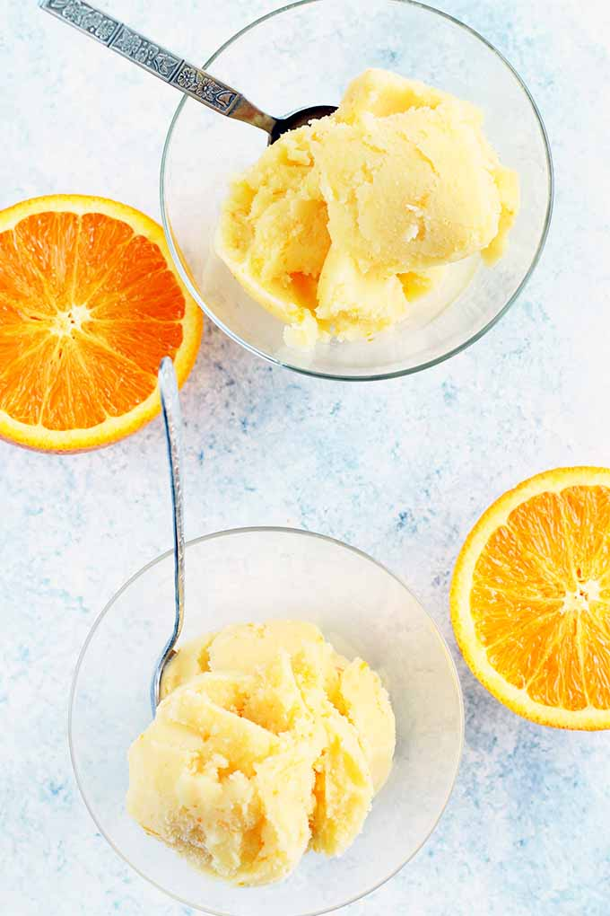 Top-down shot of two glass dishes of sherbet with spoons, on a white and pale blue sponge painted background with two orange halves.