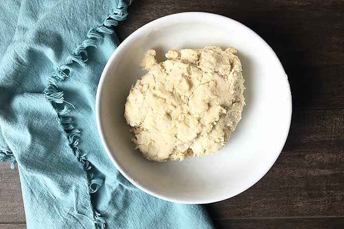Horizontal image of a bowl of dough on a blue towel.