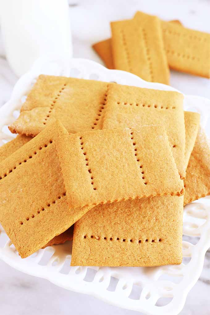 Homemade graham crackers arranged on a decorative white ceramic plate, with a bottle of milk and more golden brown crackers in the background.