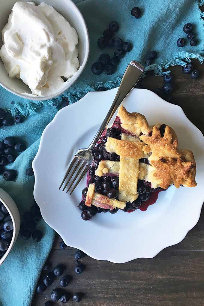 Vertical image of a white plate with a slice of pie and a fork next to bowls of blueberries and whipped cream.
