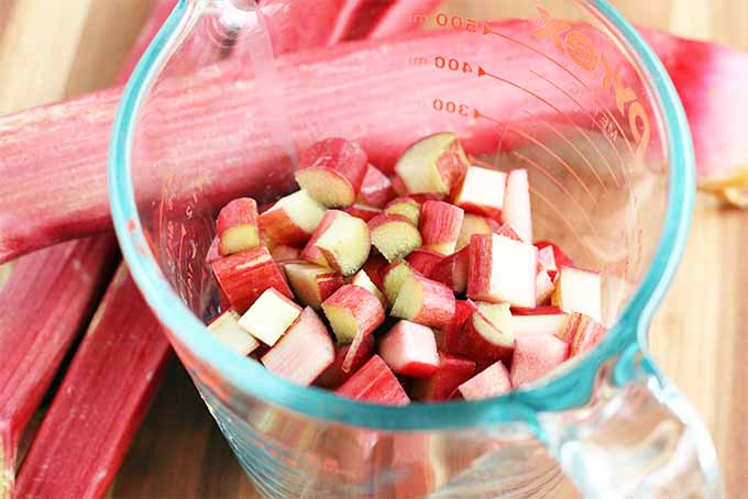 Closeup shot of a glass measuring pitcher filled with chopped rhubarb, next to three whole pinkish-red stalks on a wood background.