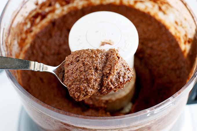 A spoonful of dark chocolate hummus is held above a food processor filled with the brown dip.
