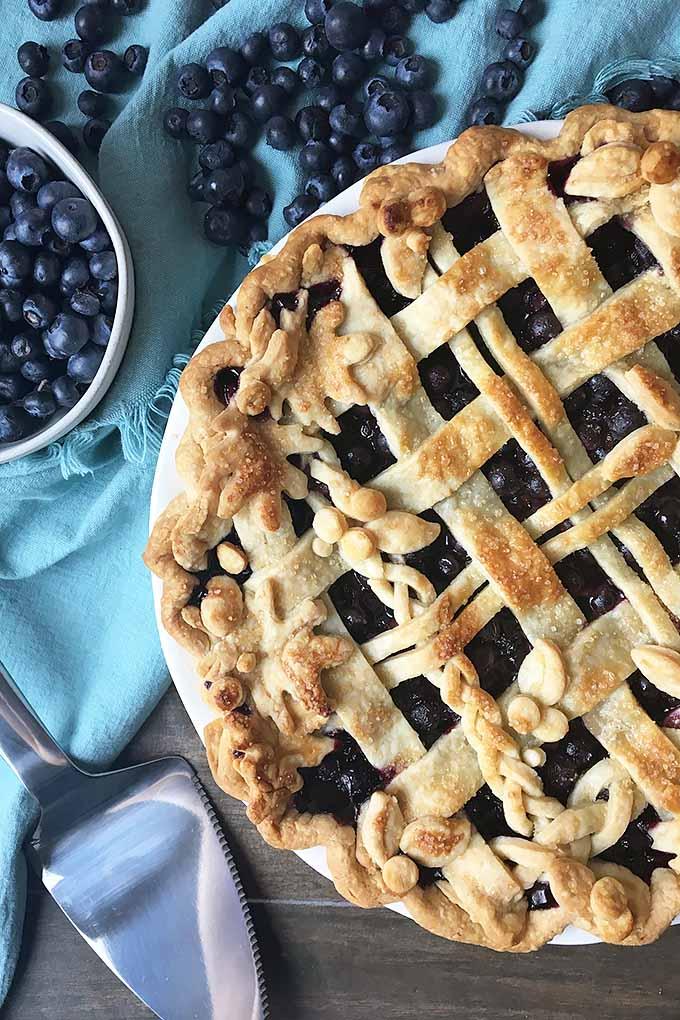Vertical closeup image of a fruit pie with lattice crust.