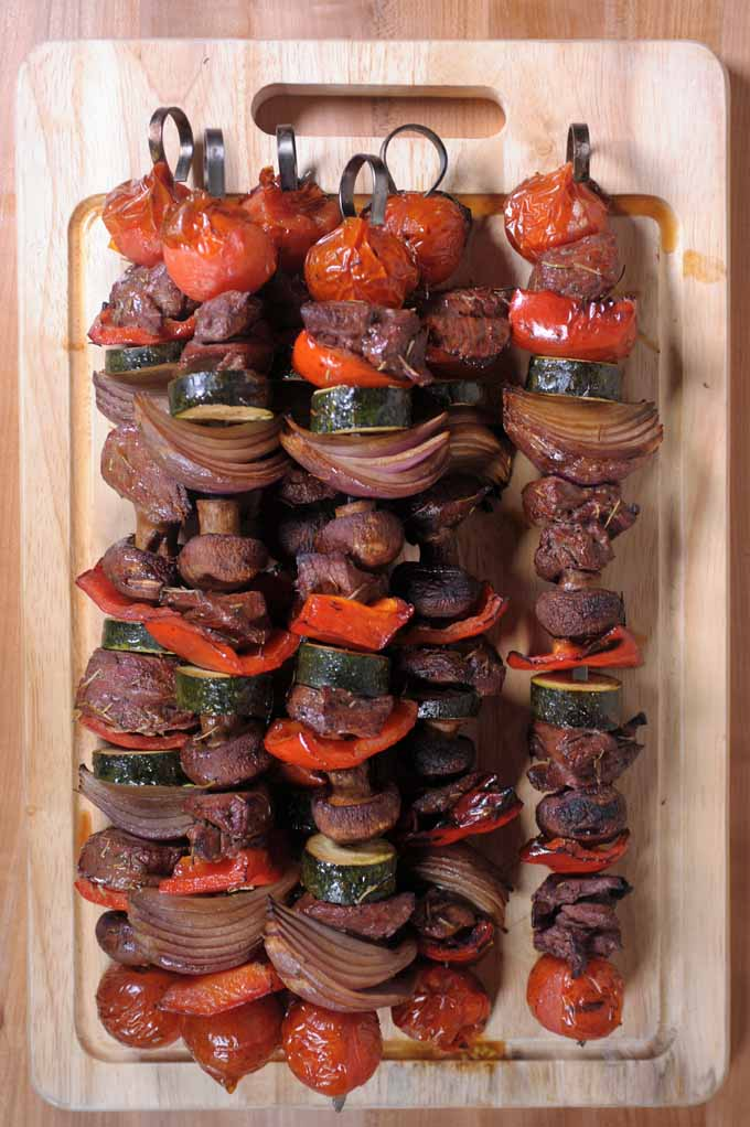 Top-down view of a dozen lamb and veggie kabobs with cherry tomatoes, mushrooms, bell pepper, zucchini, and onion, stacked on a wooden cutting board.