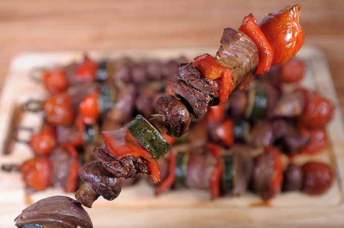 Closeup of a single skewer of lamb chunks and cherry tomatoes, onion, red bell pepper, mushrooms, and zucchini.
