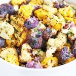 A white serving dish of chopped, roasted, multicolored cauliflower with fresh herbs, on a white marble background.