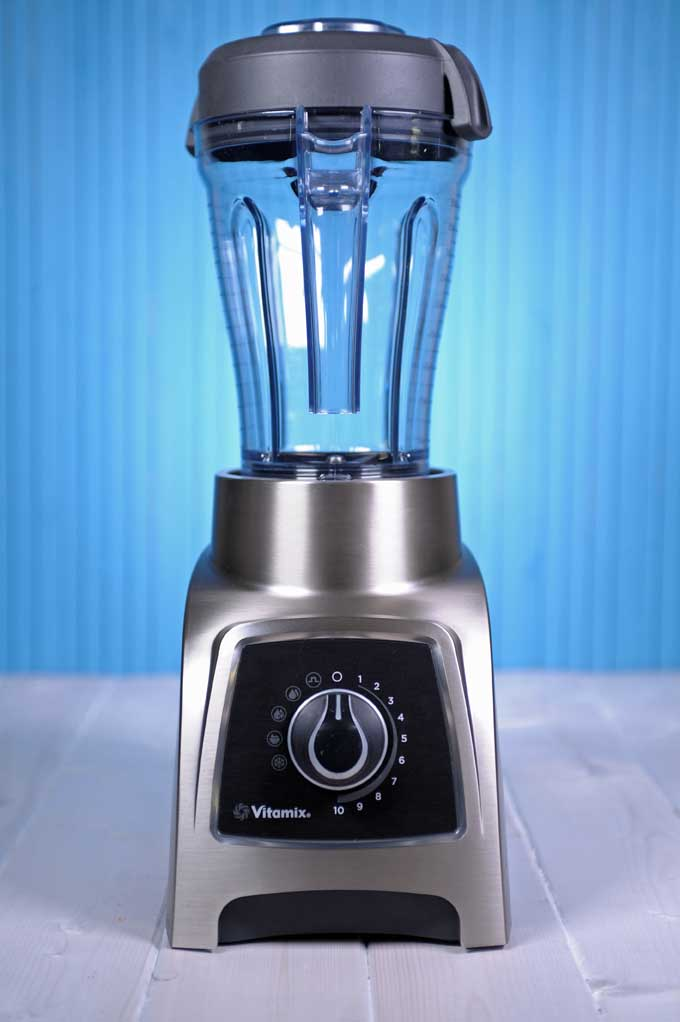 Front view of a Vitamix S55 Personal Blender with a medium blue background with back lighting. Rim lightly accents the hopper.
